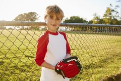 A boy holding baseball mitt and smiling to camera stock images