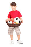 Boy holding a basket with balls Stock Images