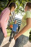 A boy holding a basketball walking towards two girls. Royalty Free Stock Image