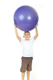 Boy holding big ball over head Stock Photography