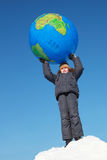 Boy holding big globe above his head Stock Photography
