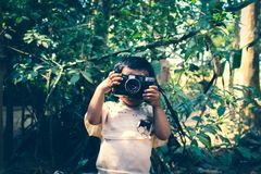 Boy Holding Black Flash Camera Near Green Leaf Plants Royalty Free Stock Photo