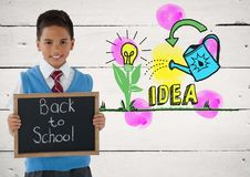 Boy holding blackboard with back to school and idea colorful graphics. Digital composite of boy holding blackboard with back to school and idea colorful graphics Royalty Free Stock Photo