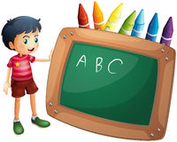 A boy holding the blackboard with crayons at the back Royalty Free Stock Photography