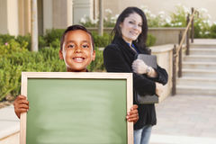 Boy Holding Blank Chalk Board on Campus with Teacher Behind Royalty Free Stock Image