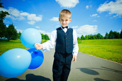 Boy holding blue balloons stock image