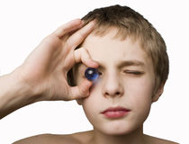 Boy holding blue marble to eye Royalty Free Stock Image