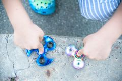 Boy holding blue and rainbow fidget spinners in his hands, view from above both gadgets spinning.  Stock Photo