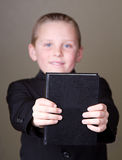 Boy holding book out stock image