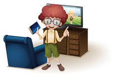 A boy holding a book standing near the blue couch Stock Photo