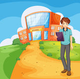 A boy holding a book standing outside the school building Stock Photo