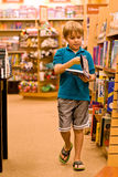 Boy holding book and walking. A seven year old boy walks in the libary, holding a book in his hands.   He wears a turquoise blue polo shirt and shorts and turns Royalty Free Stock Photography