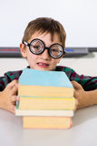Boy holding books on table in classroom. Portrait of boy holding books on table in classroom Royalty Free Stock Photography