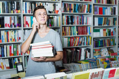 Boy holding books and talking on mobile phone in shop. Teenager boy holding books and talking on mobile phone in book shop Stock Photos