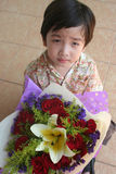 Boy holding bouquet. Little boy holding bouquet of red roses and lily Stock Images
