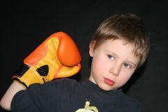 Boy holding boxing glove. A studio portrait of a boy wearing an orange boxing glove, raising his fist. Black background royalty free stock photo