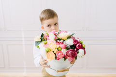 Boy holding a bucket with flowers Stock Image
