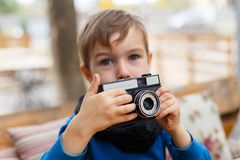 The boy is holding a camera in his hands, in a cafe. The concept of family. Close-up of a little boy Royalty Free Stock Photo