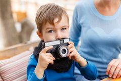 The boy is holding a camera in his hands, in a cafe. The concept of family. Close-up of a little boy Royalty Free Stock Images