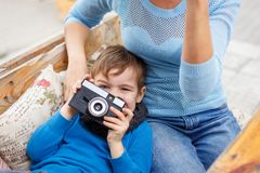 The boy is holding a camera in his hands, in a cafe. The concept of family. Close-up of a little boy Stock Photos