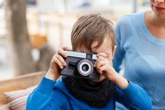 The boy is holding a camera in his hands, in a cafe. The concept of family. Close-up of a little boy Royalty Free Stock Photography