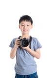 Boy holding camera over white background Stock Image