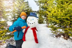 Boy holding carrot to put as nose of snowman. With red scarf and hat during sunny winter day with fir forest on the background Royalty Free Stock Image