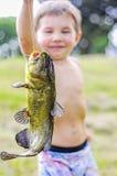 Boy holding catfish. Boy holds up large catfish on a string Stock Photo