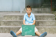 Boy holding Chalkboard with words Second Grade. Outdoor photo Stock Images