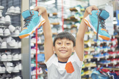 Boy holding chosen shoes smiling in store Royalty Free Stock Image