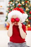 Boy holding Christmas decoration in front of eyes Royalty Free Stock Image