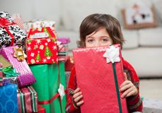 Boy Holding Christmas Gift In Front Of Face Royalty Free Stock Image