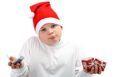 Boy holding Christmas presents and euro money. Portrait of small boy wearing red Santa Claus cap, with little Christmas presents and some money in his hands Royalty Free Stock Photography