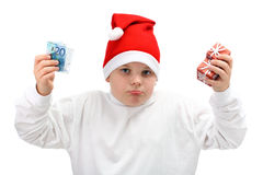 Boy holding Christmas presents and euro money. Portrait of small boy wearing red Santa Claus cap, with little Christmas presents and some money in his hands Royalty Free Stock Images
