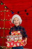 Boy holding Christmas presents. Little boy holding Christmas presents stock photography