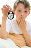 Boy is holding  clock. Little boy is holding clock while yawning Royalty Free Stock Photography