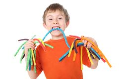 Boy holding colorful licorice candy. A young boy has hands full of candy and one in his mouth Royalty Free Stock Photo