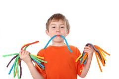 Boy holding colorful licorice candy. A young boy holds bunches of colorful licorice Royalty Free Stock Image