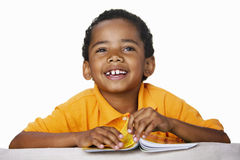 Boy holding comic, smiling, cut out Stock Photography