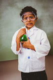 Boy holding conical flask in classroom. Portrait of cute boy holding conical flask in the classroom Royalty Free Stock Photography