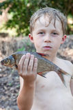 Boy holding a dead fish Royalty Free Stock Photography