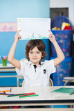 Boy Holding Drawing Paper At Desk In Kindergarten Stock Photo