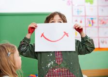 Boy Holding Drawing Paper On Face In Art Class Royalty Free Stock Images