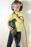 Boy holding drill upright Royalty Free Stock Photo