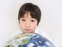Boy holding earth. Asian boy holding earth ball smiling Royalty Free Stock Photo