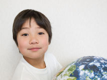 Boy holding earth. Asian boy holding earth ball smiling Royalty Free Stock Image