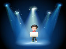 A boy holding an empty board with spotlights Royalty Free Stock Images