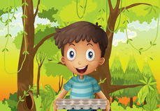 A boy holding an empty eggtray in the forest Stock Photography