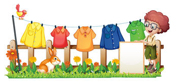 A boy holding an empty frame in front of the hanging clothes Stock Image