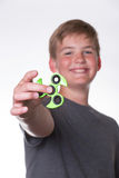 Boy holding fidget spinner. Young teenage boy holding fidget spinner in front of his face stock photography